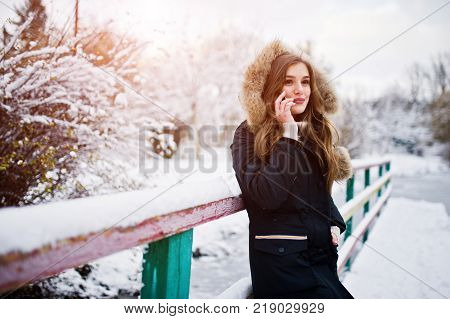 Beautiful Brunette Girl In Winter Warm Clothing. Model On Winter Jacket Against Green Wooden Backgro