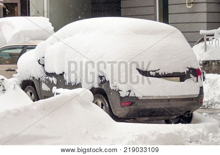 Car covered with first snow. Car buried under the snow and frozen. Bank of snow in winter