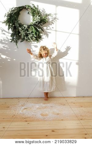 Playful little blonde female child in white dress, throws artificial snow in air, poses in white cozy room with symbolic Christmas garland on wall, enjoys winter holidays. Children, emotions concept.