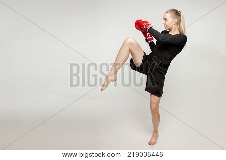 Beautiful athletic girl with boxing gloves hit high foot.