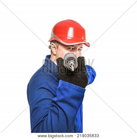 Worker holding electric drill and wearing hard hat. Aims drill. Isolated on white