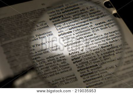 CLECKHEATON, WEST YORKSHIRE, UK: MAGNIFYING GLASS ON DICTIONARY PAGE SHOWING DEFINITION OF THE WORD ARBITRATE, CIRCA 2006, CLECKHEATON, WEST YORKSHIRE, UK