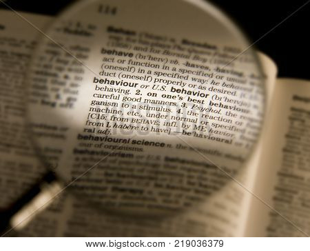 CLECKHEATON, WEST YORKSHIRE, UK:MAGNIFYING GLASS ON DICTIONARY PAGE SHOWING DEFINITION OF THE WORD BEHAVIOUR, CIRCA 2005, CLECKHEATON, WEST YORKSHIRE, UK
