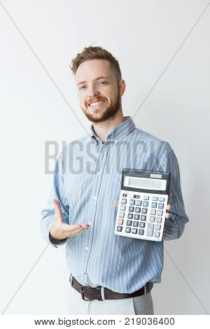 Portrait of attractive smiling young man holding calculator with presenting gesture. Financial manager showing profit. Finance concept