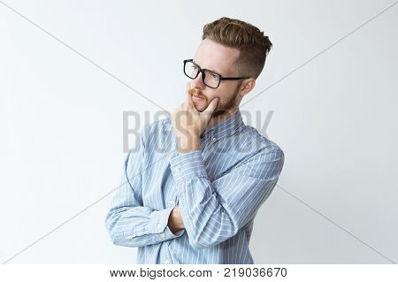 Portrait of attractive young man in deep thoughts keeping hand on chin. Businessman pondering deal. Decision making concept.