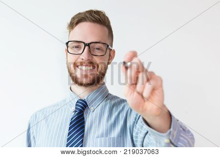 Closeup portrait of handsome young businessman writing on glass board. Businessman signing lucrative contract. Business success or presentation concept