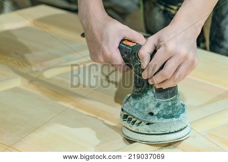 Сarpenter polishes the wooden surface of the door leaf. Electric eccentric orbital grinding machine. Mechanized woodworking carpenter hand tool in working carpentry workshop.