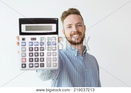 Portrait of attractive content young man holding calculator. Successful young broker showing profit. Finance concept.