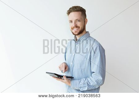 Portrait of attractive content young man estimating with calculator and looking at camera. Banker calculating profit for client. Finance concept.