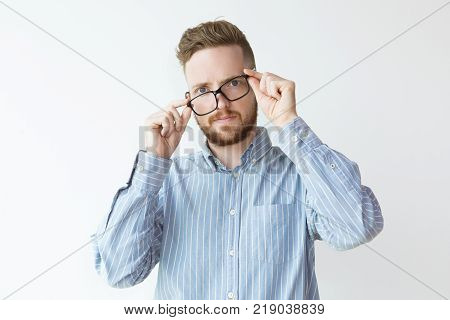 Portrait of attractive shocked young man wearing glasses incorrectly. Businessman discovering new unexpected way for development. Good or bad news concept.