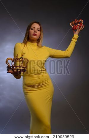Young Woman In Yellow Evening Dress Holds In Hands Two Crowns