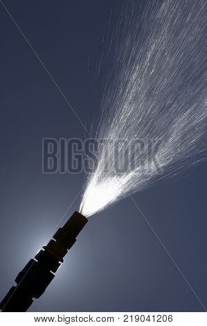 Jet Of Water Spraying From Garden Hose Pipe In Summer Sun