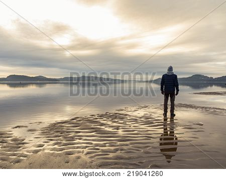 Man standing at the beach in the Norwegian fjord Tovdalsfjorden, looking at the calm sea and the mist and fog. Sand patterns and reflections of the man in the water. Hamresanden, Kristiansand, Norway