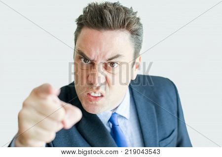 Closeup of angry middle-aged business man looking at camera and pointing finger at viewer. Isolated front view on white background. Dissatisfaction concept.