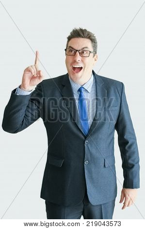 Closeup portrait of cheerful middle-aged business man pointing finger upwards. Isolated front view on white background. New idea concept.
