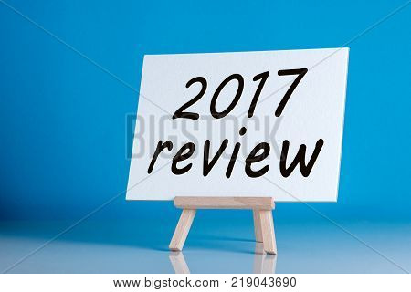 poster of 2017 review - poster with an inscription on a blue background. Time to summarize and plan goals for the next year. Business background.