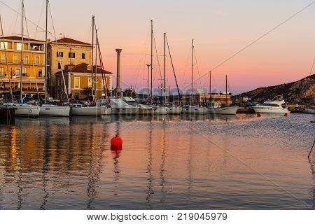 Boats in La Maddalena harbor at sunset Sardinia