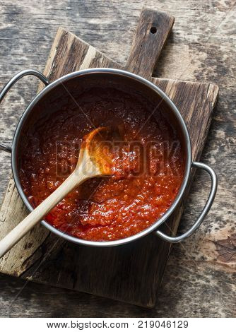 Classic homemade tomato sauce in the pan on a wooden chopping board on brown background top view. Pasta pizza tomato sauce. Vegetarian food