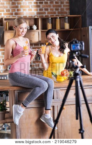 Healthy nutrition. Cheerful positive delighted women sitting together and drinking fresh orange juice while leading healthy lifestyle