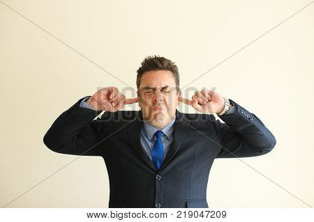 Annoyed sullen businessman covering ears to protect them from noise. Furious frowning male executive suffering from emotional stress. Defense of bad information concept