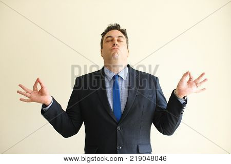 Funny expressive businessman meditating to relax and touching fingers to feel peaceful. Grimacing concentrated male executive trying to calm down. Zen-like calm concept