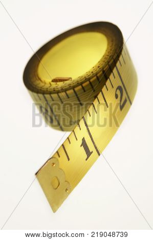 Yellow Coiled Tape Measure With Imperial Inch Measurements On White Background