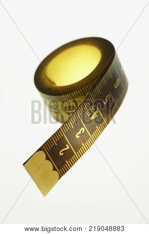 YELLOW COILED TAPE MEASURE WITH METRIC MEASUREMENTS ON WHITE BACKGROUND