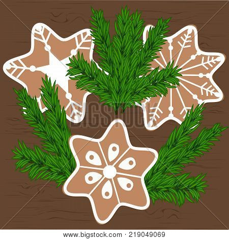 Christmas cookies and branches of a Christmas tree on a wooden background