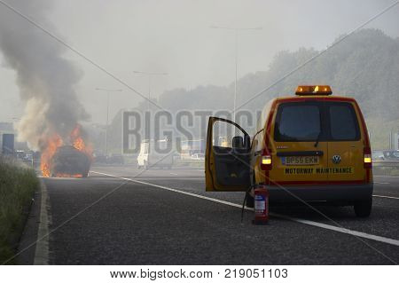M62 MOTORWAY, WEST YORKSHIRE, UK: EMERGENCY SERVICES VEHICLE WITH FIRE EXTINGUISHER AT SCENE OF BURNING CAR ON HARD SHOULDER OF MOTORWAY CIRCA 2006, M62 MOTORWAY, WEST YORKSHIRE, UK