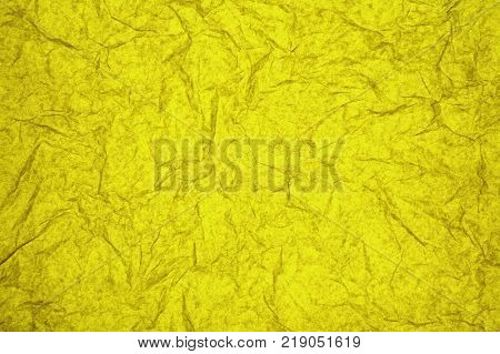 ABSTRACT RANDOM BACKGROUND OF CREASED CRUMPLED YELLOW TISSUE PAPER
