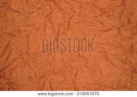 ABSTRACT RANDOM BACKGROUND OF CREASED CRUMPLED ORANGE TISSUE PAPER
