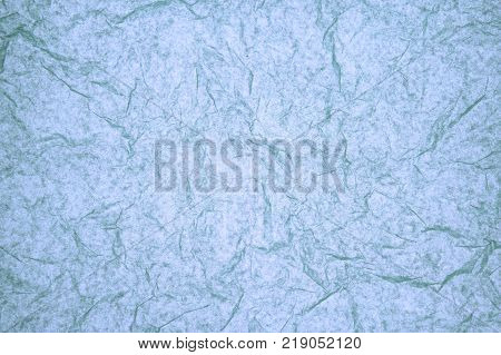 ABSTRACT RANDOM BACKGROUND OF CREASED CRUMPLED LIGHT BLUE TISSUE PAPER