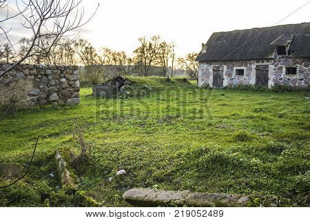 The farmyard is an agricultural abandoned farm. The old collapsed barns. The entrance to the cellar is like a cave. Late autumm . Podlasie Poland.