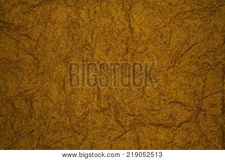 ABSTRACT RANDOM BACKGROUND OF CREASED CRUMPLED BROWN YELLOW TISSUE PAPER