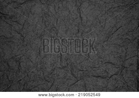 ABSTRACT RANDOM BACKGROUND OF CREASED CRUMPLED DARK GREY TISSUE PAPER