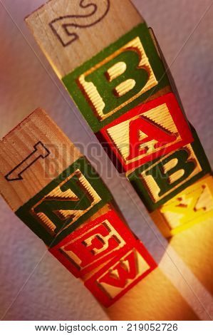 STACK OF WOODEN TOY BUILDING BLOCKS SPELLING THE WORDS NEW BABY