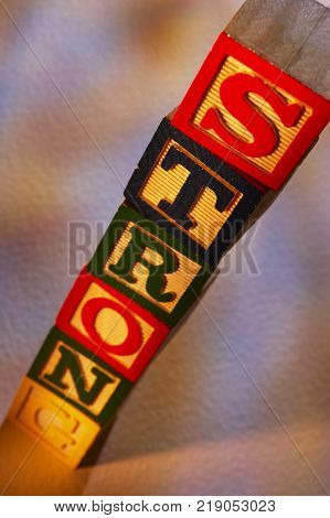 STACK OF WOODEN TOY BUILDING BLOCKS SPELLING THE WORD STRONG