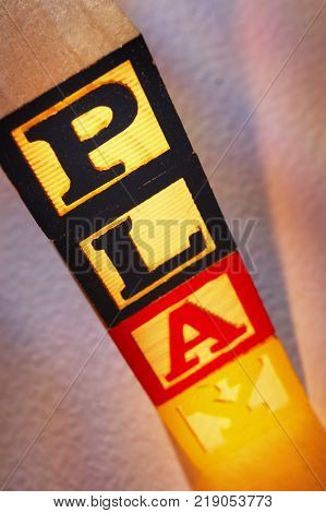 STACK OF WOODEN TOY BUILDING BLOCKS SPELLING THE WORD PLAY