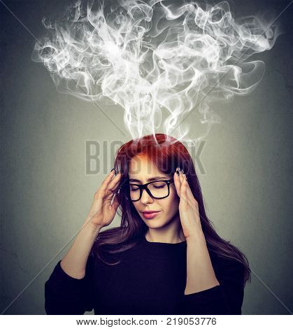 Portrait young stressed woman thinking too hard steam coming out up of head isolated on gray wall background. Face expression emotion perception