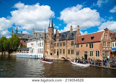 Bruges, Belgium - April 17, 2017: Tourist boat on canal in Bruges in a beautiful summer day, Belgium