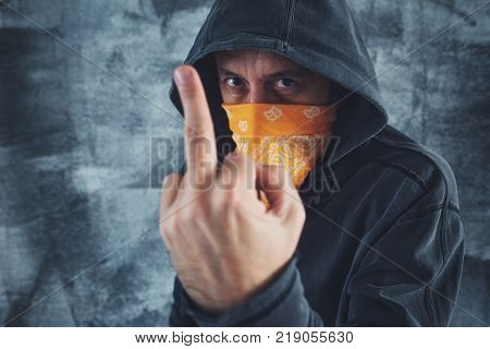 Hooded gang member criminal with scarf over face showing middle finger