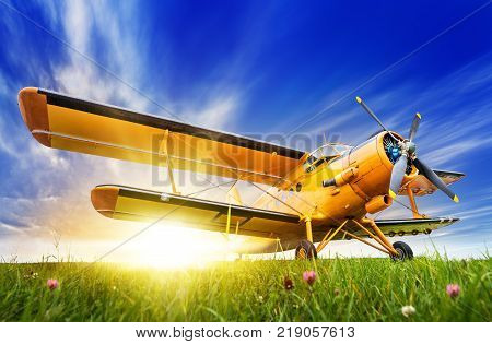 historic biplane on a meadow against a sunset