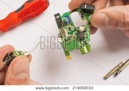 board in hands on a white background with a red screwdriver and interchangeable tips with a screwdriver