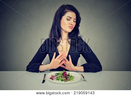 Young disgusted woman hates and rejects vegetarian diet