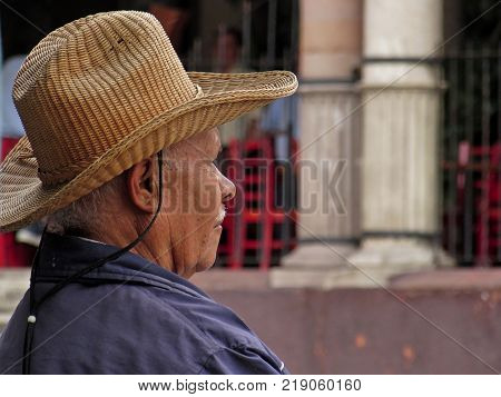 San Miguel de Allende, Guanajuato / Mexico - September 17 2015: Man with hat relaxed and gazing in the downtown area of San Miguel de Allende