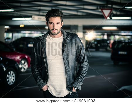 Handsome muscular man in casual clothing on background of parking.
