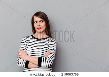 Portrait of a confused woman standing with arms folded and looking away at copyspace isolated over gray background