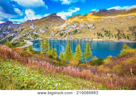 The concept of ecological and extreme tourism. Glacial lake with clear cold water. Mountain Lake Lago di Fedaia, Dolomites