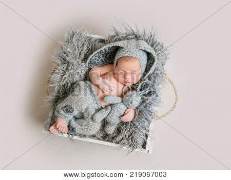Baby boy in bunny costume sleeping.
