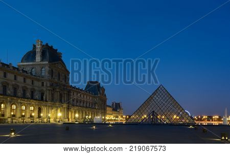 PARIS, FRANCE - DECEMBER 11 2017: View of famous Louvre Museum with Louvre Pyramid at evening. Louvre Museum is one of the largest and most visited museums worldwide